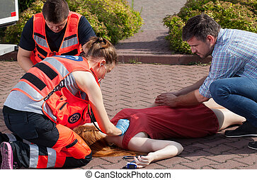 Couple of paramedics examining woman on the street