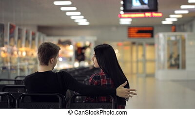 Couple of people actively talks with each other sitting in airport