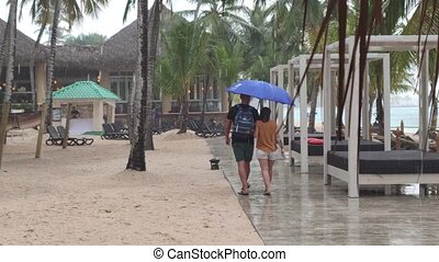 Couple of people stroll in the Caribbean resort in a Rainy ...