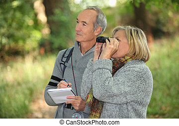 couple of retirees observing wildlife with binoculars in...