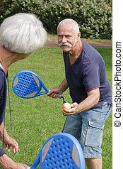 couple of seniors playing tennis