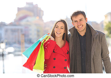 Couple of shoppers walks in winter holding shopping bags