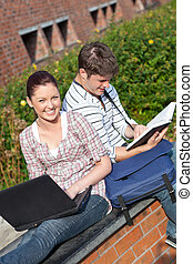 Couple of students working together with book and laptop