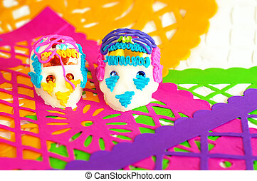 couple of sugar skulls on white yellow purple green and pink perforated paper