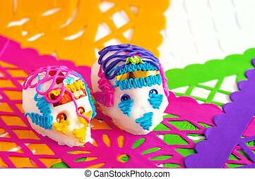 couple of sugar skulls on yellow purple green and pink perforated paper