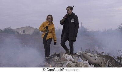 Couple of survivors with weapons in the smoky and unkind...