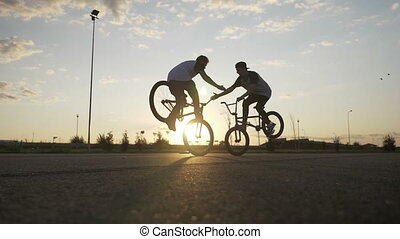 Couple of teen bikers doing high five while performing an...