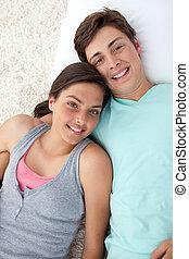 Couple of teenagers lying on the floor