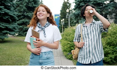 Couple of teenagers walking outdoors talking holding books drinking coffee