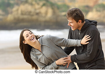Couple of teens joking and flirting on the beach