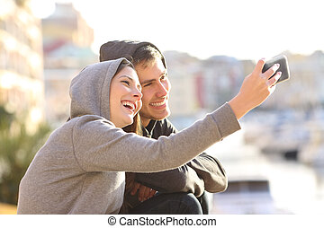 Couple of teens taking a selfie outdoors
