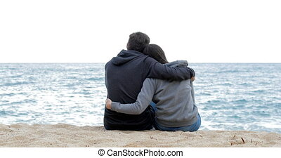 Couple of teens watching the ocean on the beach