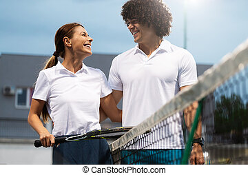 Couple of tennis players smiling at the court after a match