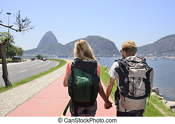 Couple of tourists backpackers walking through Rio de...