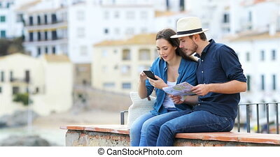 Couple of tourists browsing booking hotel on vacation
