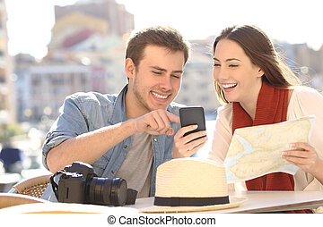 Couple of tourists comparing online guide and map