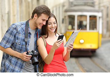 Couple of tourists consulting guide online - Couple of...
