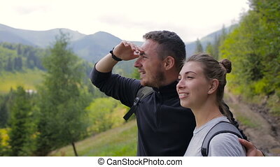 Couple of tourists looking out into the distance in the mountains