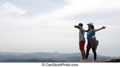 Couple Of Tourists On Mountain Top With Raised Hands Enjoy...