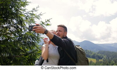 Couple of tourists take pictures together in the afternoon in the mountains