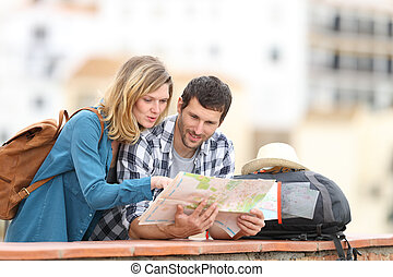 Couple of tourists talking checking map on vacation