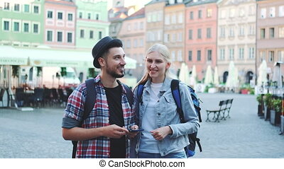 Couple of tourists using smartphone and admiring beautiful surroundings. They going sightseeing early in the morning.