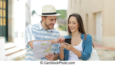 Couple of tourists walking and booking hotel online