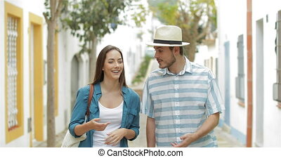 Couple of tourists walking and talking in a town street on...