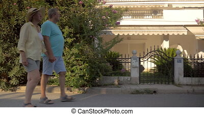 Couple of tourists walking by private houses - Senior man...