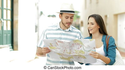 Couple of tourists walking checking map in a town street