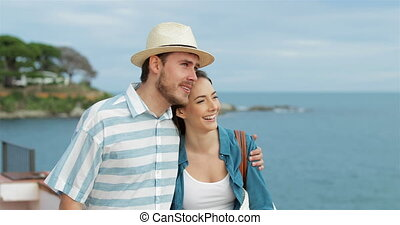 Couple of tourists walking contemplating the beach - Happy...