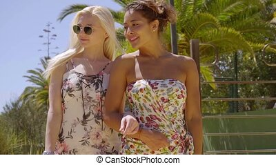 Couple of trendy attractive young women walking arm in arm...