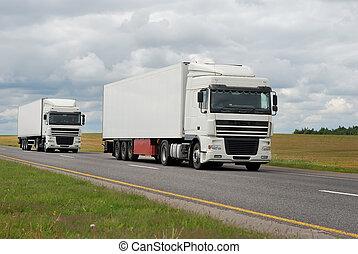 couple of white trucks on highway