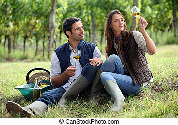 Couple of winegrowers with glasses of wine