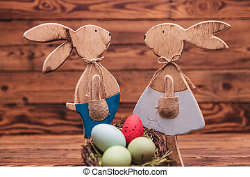 couple of wooden easter bunnies standing near eggs basket