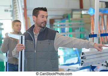 couple of workmen inspecting window frames at factory indoor