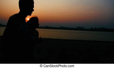 Couple of young adult athletes: woman and man running along promenade of river at sunset, silhouette.