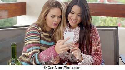 Couple of Young Girlfriends checking their phone - Couple of...