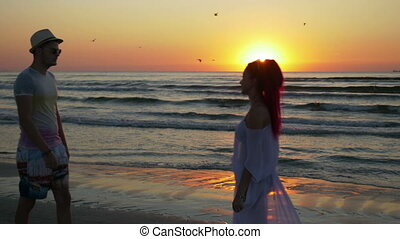 Couple of young man and woman meeting on a sandy beach and kissing with passion at sunrise