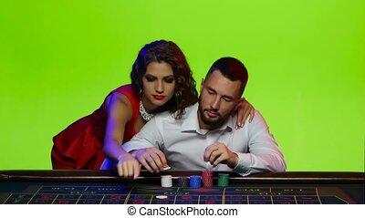 Couple of young people make bets at the poker table