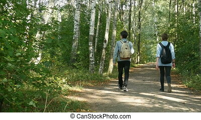 couple of young people walks in the park