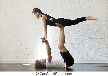 Couple Of Young Sporty People Practicing Yoga Lesson With