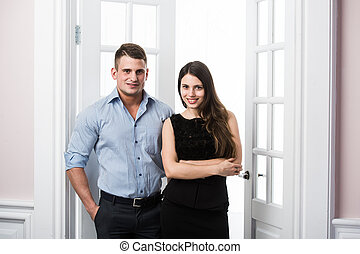 Couple of  young stylish business people in the doorway home interior loft office
