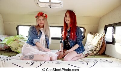 couple of young women sitting on the couch in autotrailer