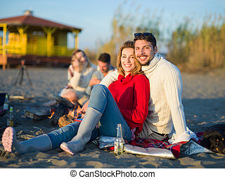 couple on a beach at autumn sunny day