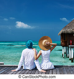 Couple on a beach jetty at Maldives - Couple on a tropical ...