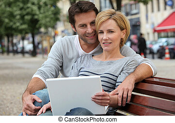 couple on a bench with laptop