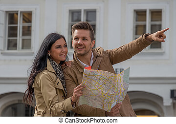 couple on a city break - young couple with map and guide ...