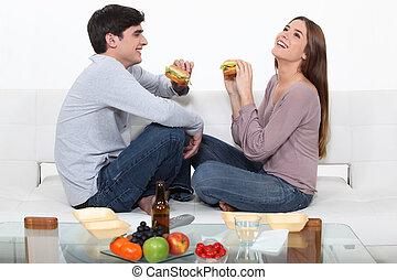 Couple on a date enjoying sandwich.