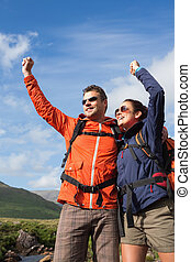 Couple on a hike cheering and smiling